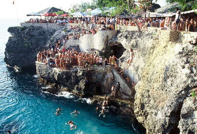 People diving off Ricks Cafe's cliffs